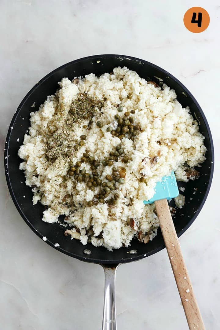greek cauliflower rice cooking a black skillet with the number 4 in the top