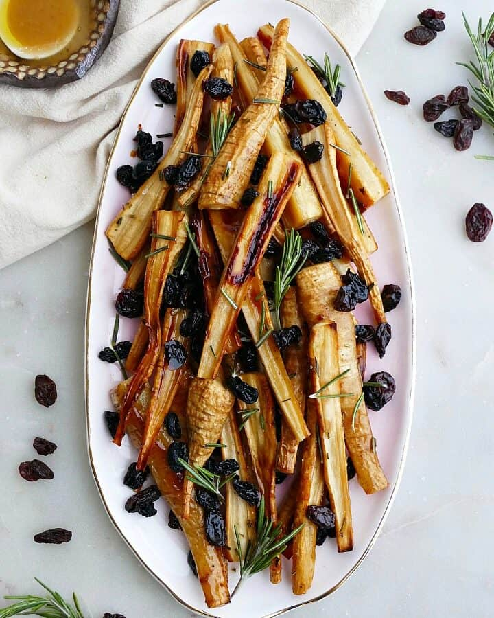 honey roasted parsnips and raisins on a pink oval tray on a white counter
