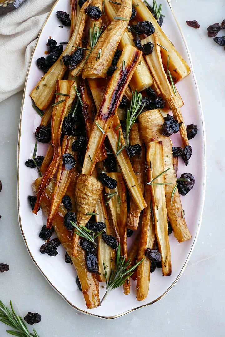 honey roast parsnips and raisins on a pink oval tray on a counter