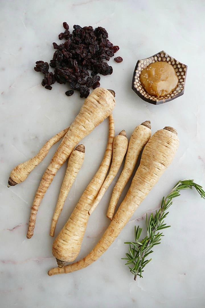 raisins, 7 parsnips, honey, and rosemary on a white counter
