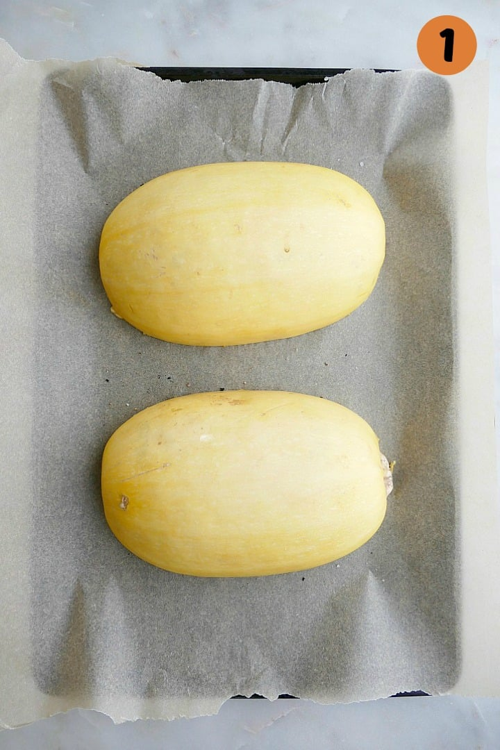 two spaghetti squash halves on a lined baking sheet on a counter