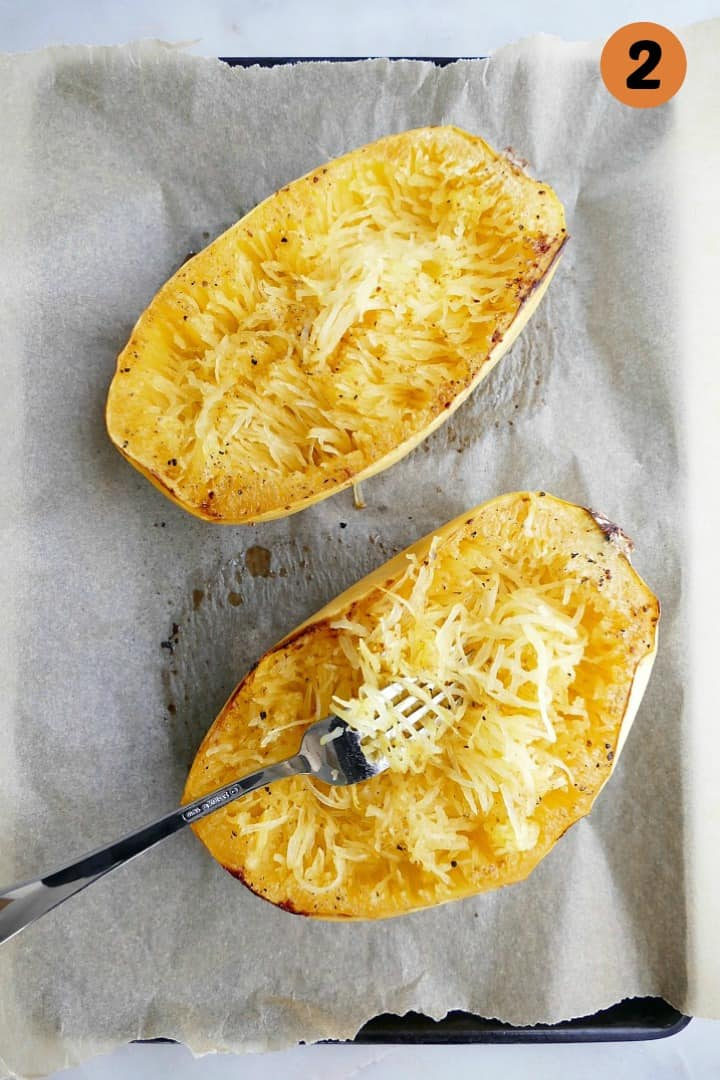 two cooked spaghetti squash halves with a fork in one of them