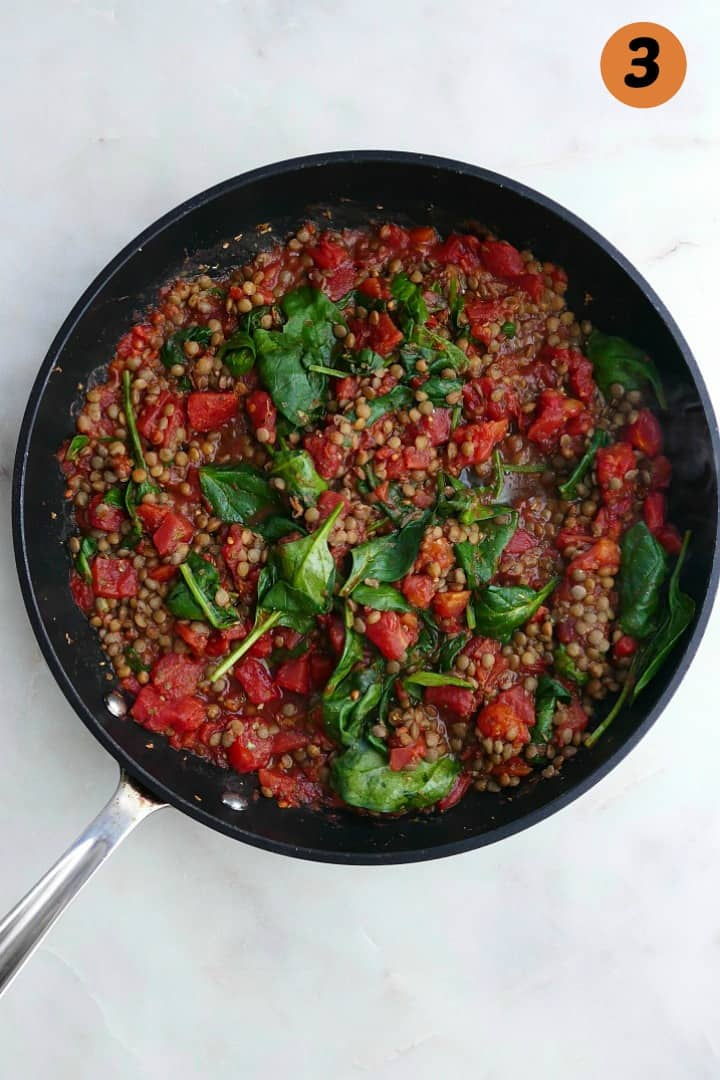 tomatoes, lentils, spinach, and seasonings cooking in a black skillet on a counter
