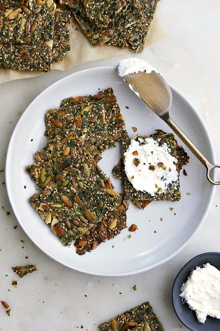 5 seed and kale crackers on a white plate with cream cheese spread on a cracker