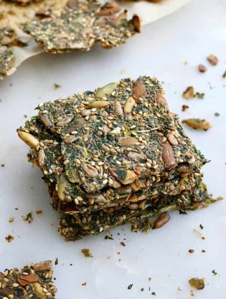 4 kale crackers stacked on top of each other on a white counter