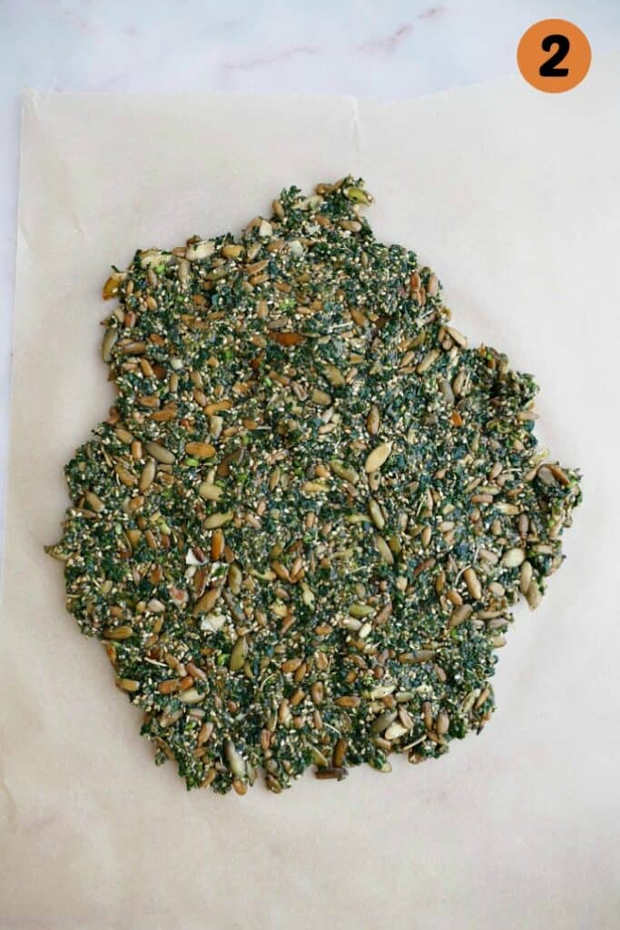 mixture for kale crackers on a piece of parchment paper on a white counter
