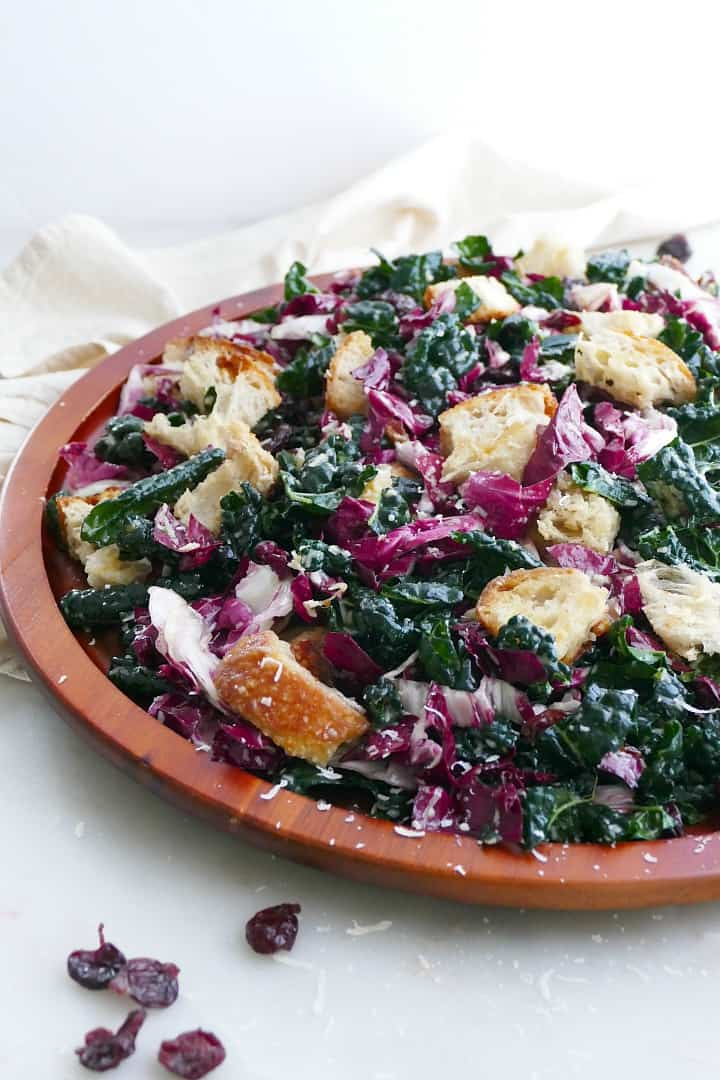 side view of kale radicchio salad and sourdough croutons on a wooden platter