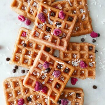 8 pink waffles on a white counter with a variety of toppings