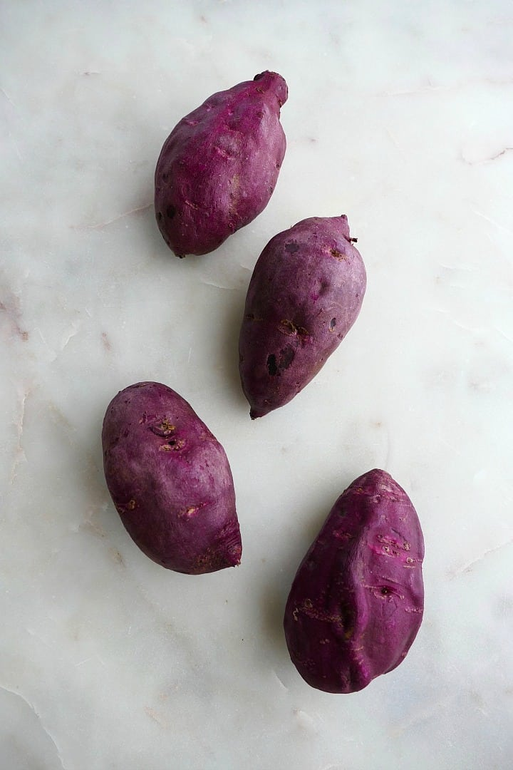 4 purple sweet potatoes next to each other on a white counter