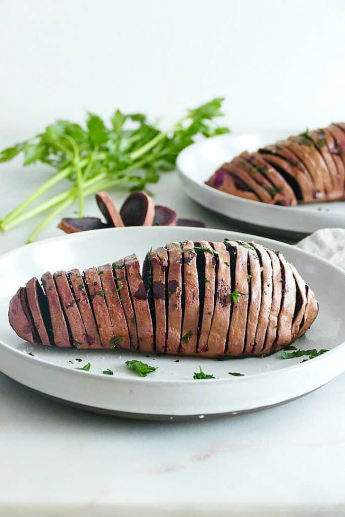 hasselback purple sweet potato on a white plate with parsley in the background