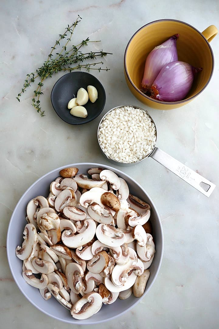 sliced mushrooms, arborio rice, shallots, garlic, and thyme on a white counter