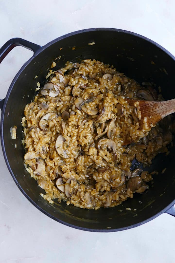 creamy vegan mushroom risotto in a black dutch oven with a wooden spoon