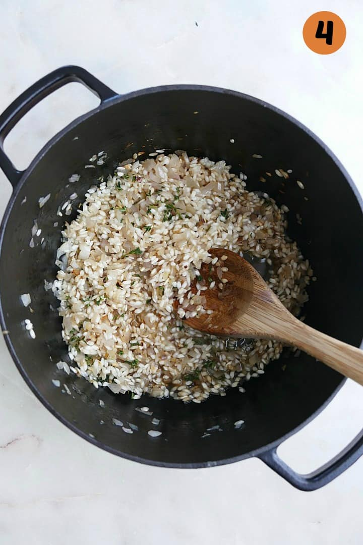 arborio rice, shallots, wine, and thyme in a black dutch oven with a spoon