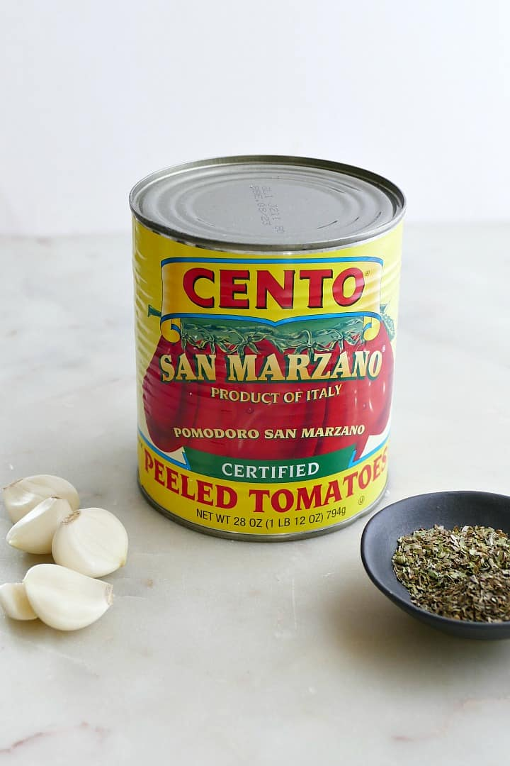 a can of cento san marzano tomatoes surrounded by garlic and herbs
