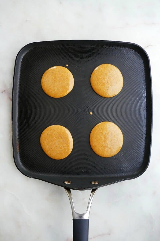 4 silver dollar pancakes on a black square skillet on a counter