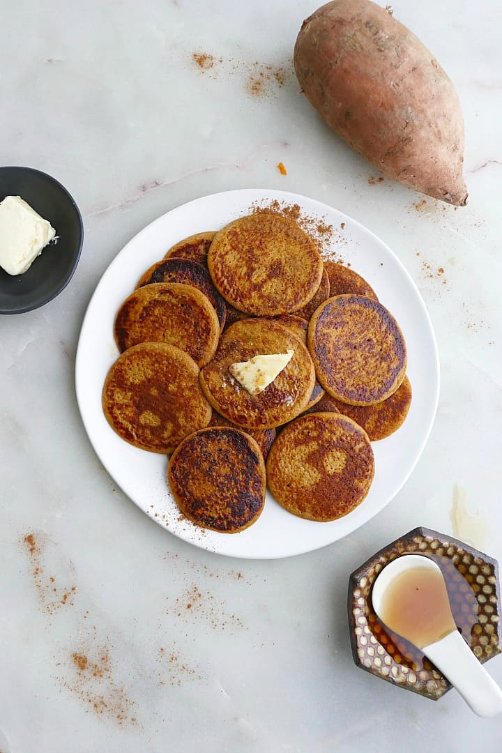 pile of silver dollar sweet potato pancakes on a white plate on a counter