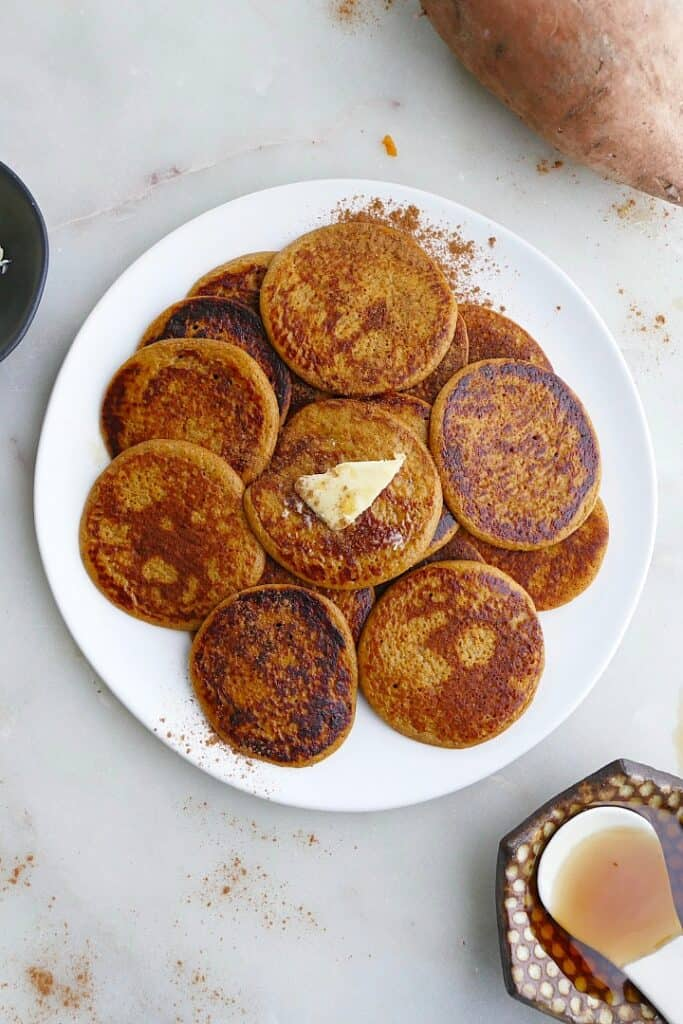 close up of a white plate with several sweet potato pancakes with a slab of butter