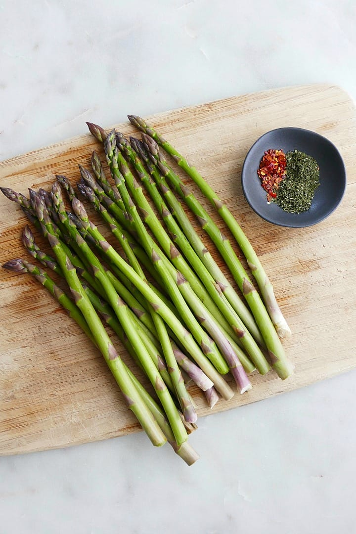 a bunch of asparagus spears spread on a bamboo cutting board next to spices
