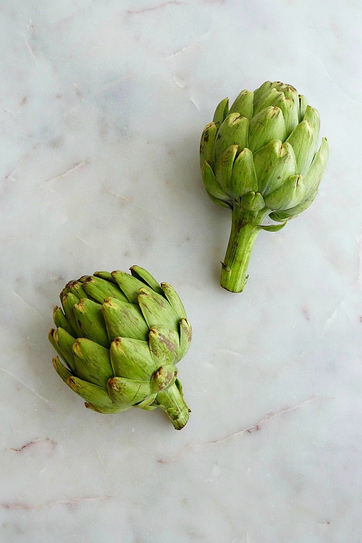 two green heirloom artichokes next to each other on a white counter