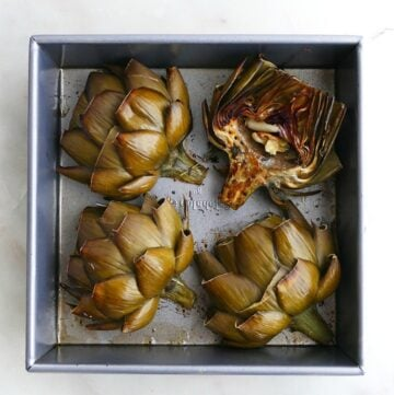 4 artichokes in a square baking dish on a white counter