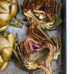 close up of two roasted artichoke halves in a silver baking dish