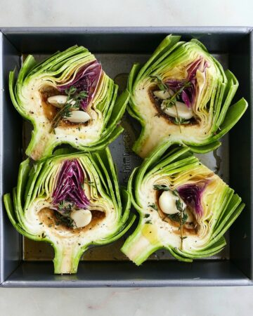square image of 4 artichoke halves stuffed with garlic in a baking dish