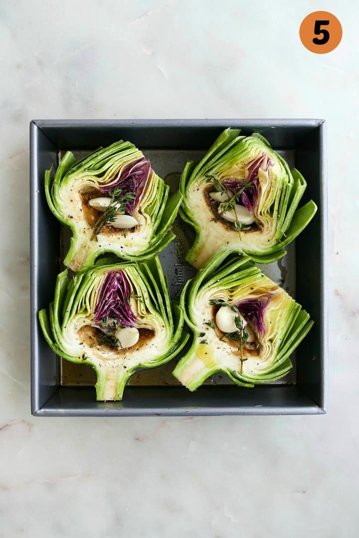 4 artichoke halves stuffed with garlic in a square baking dish