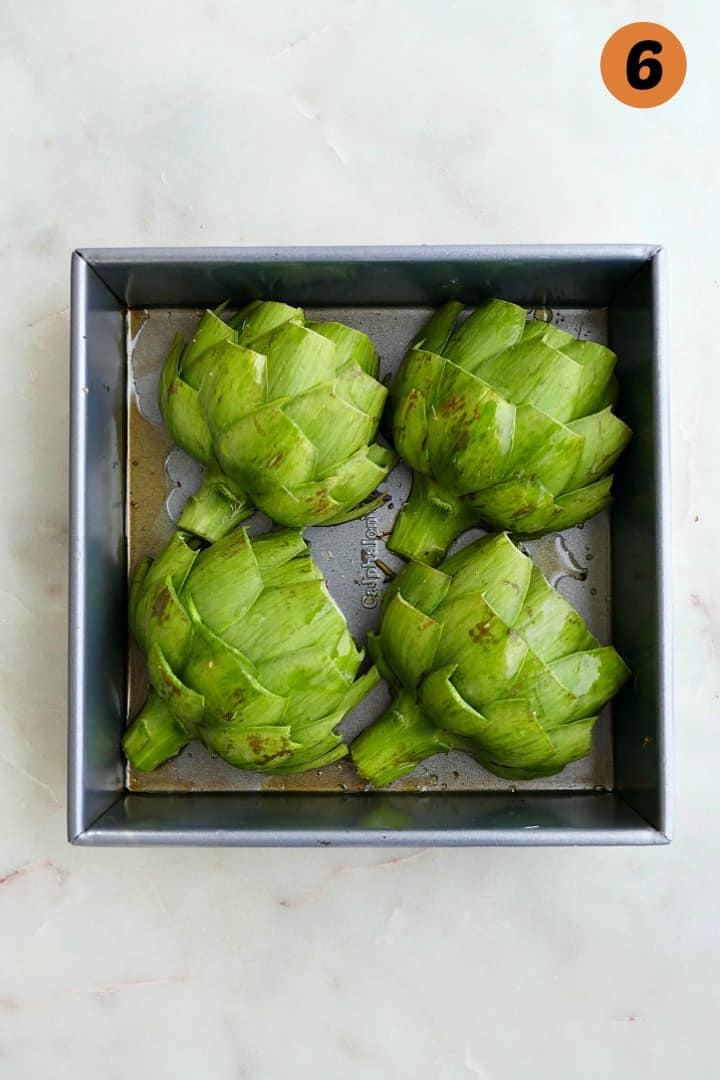 4 artichoke halves in a square baking dish on a white counter