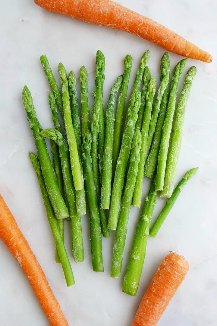 one bunch of asparagus and three carrots spread out on a white counter