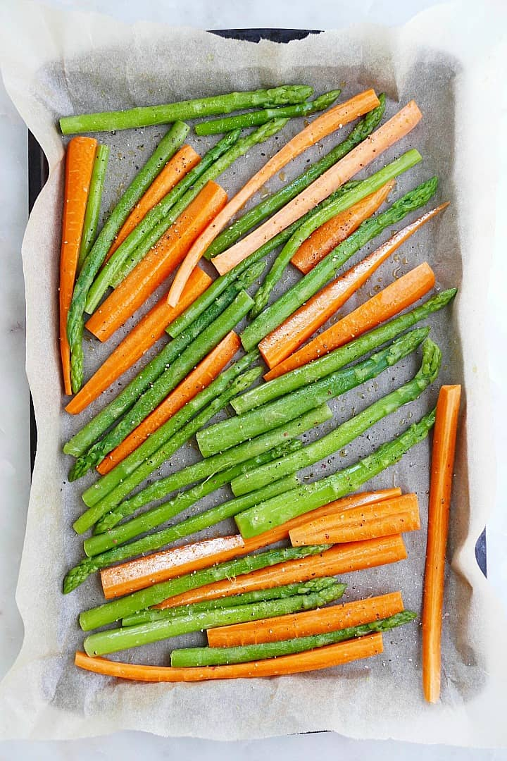 asparagus spears and carrot slices on a baking sheet lined with parchment paper