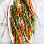roasted asparagus and carrots on an oval tray on top of a counter