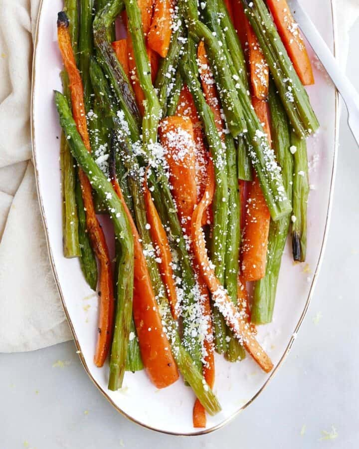 square image of roasted asparagus and carrots on a pink oval tray