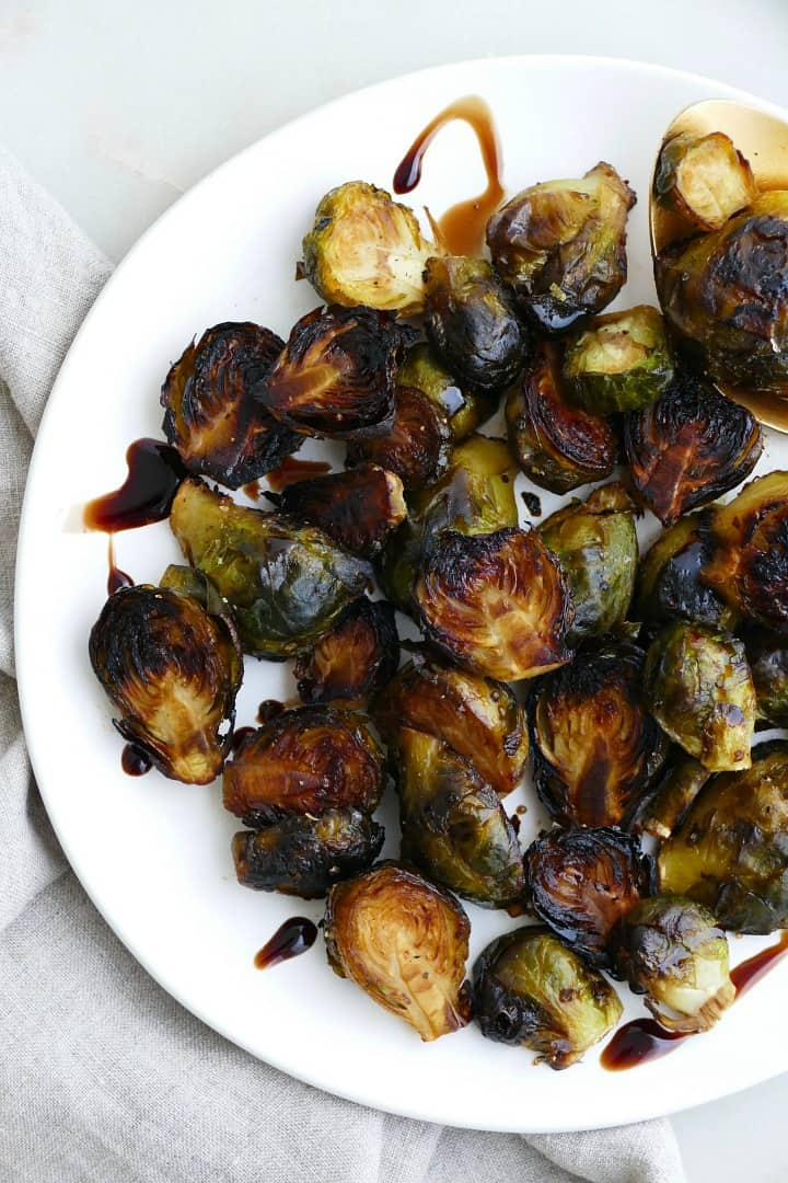 crispy brussel sprouts tossed in balsamic reduction on a white plate