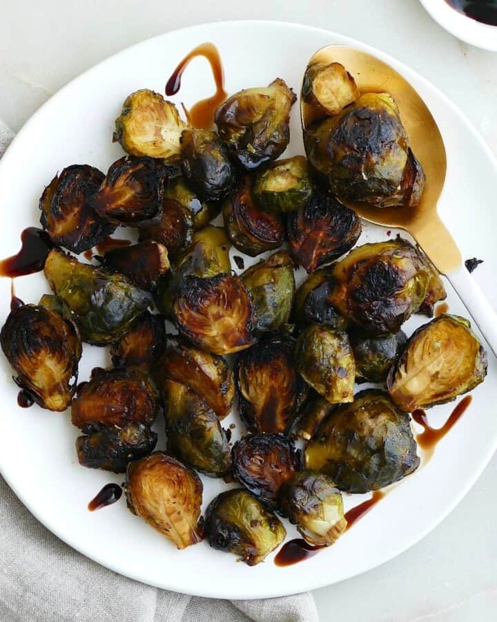 square image of roasted frozen brussels sprouts on a white plate