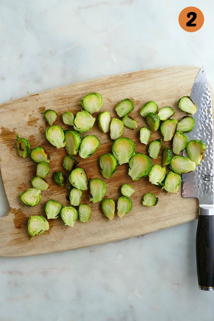 brussels sprouts cut in half on a bamboo cutting board with a chef's knife