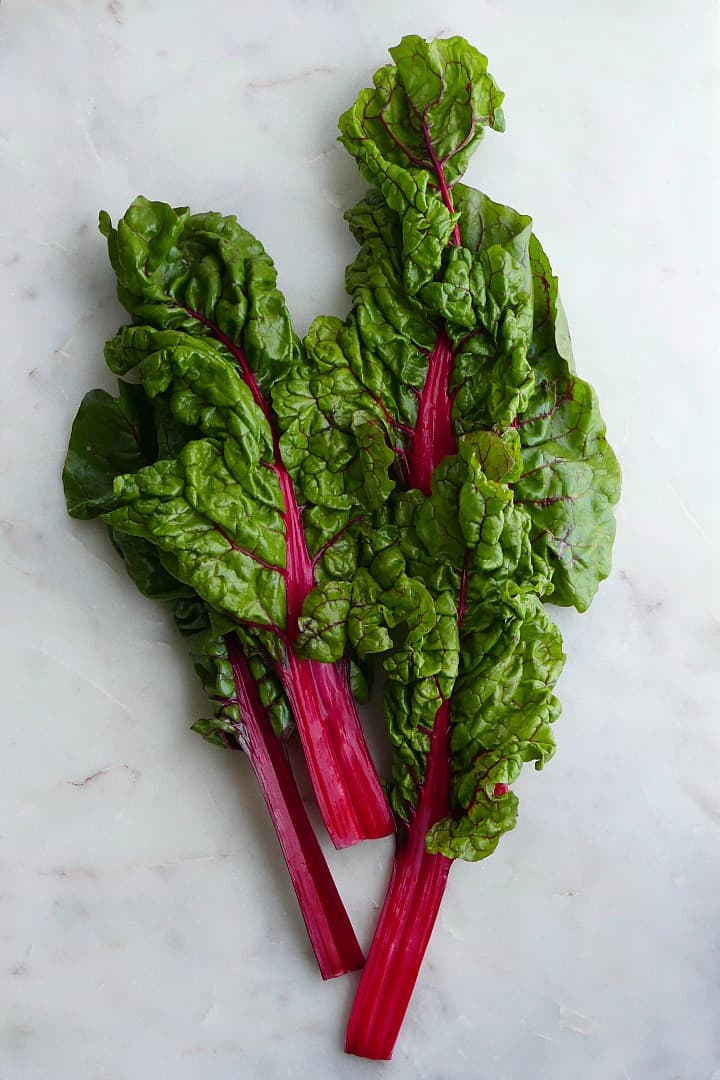 three large pieces of swiss chard with red stems on a white counter