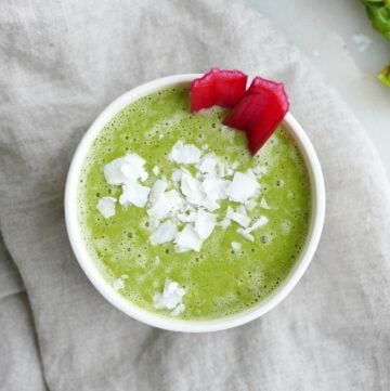 square image of swiss chard smoothie topped with coconut flakes