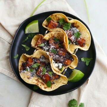 square image of three black bean sweet potato tacos on a black plate on a yellow napkin