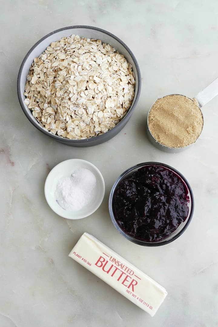 oats, salt, brown sugar, blueberry jam, and butter on a white counter