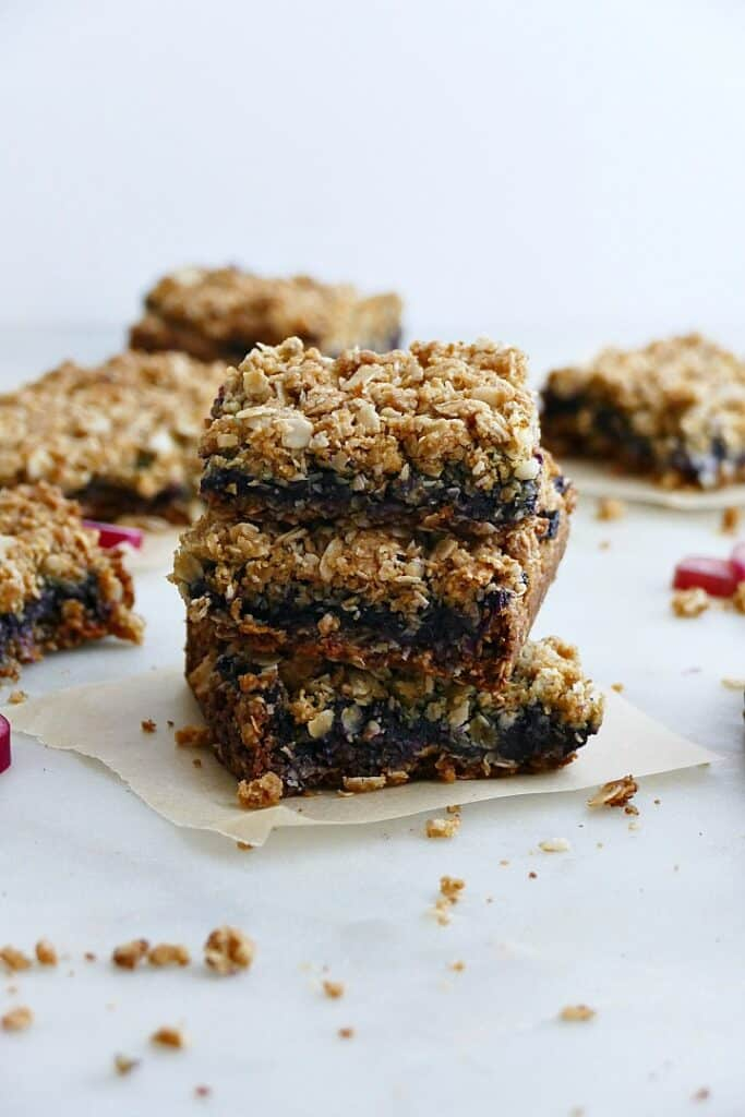 three blueberry rhubarb bars on top of each other on a white counter