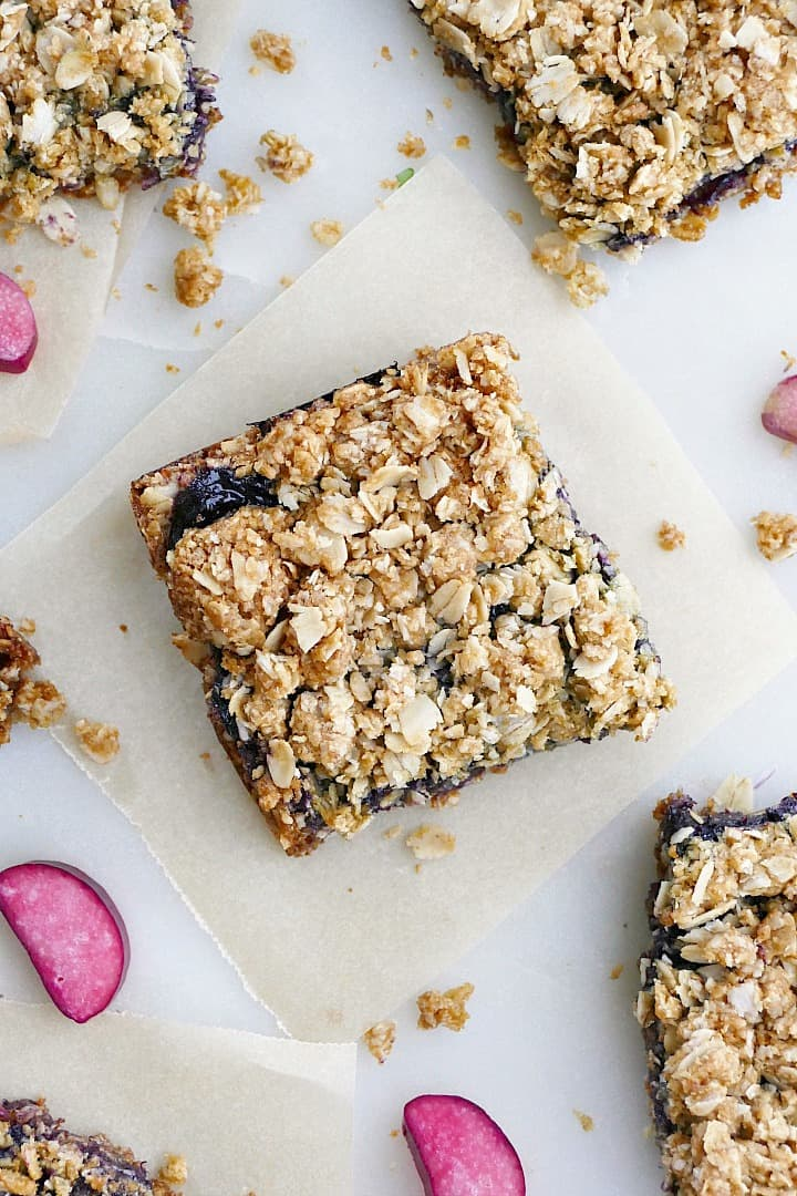 blueberry rhubarb crumb bars spread out on a counter with oats and rhubarb slices