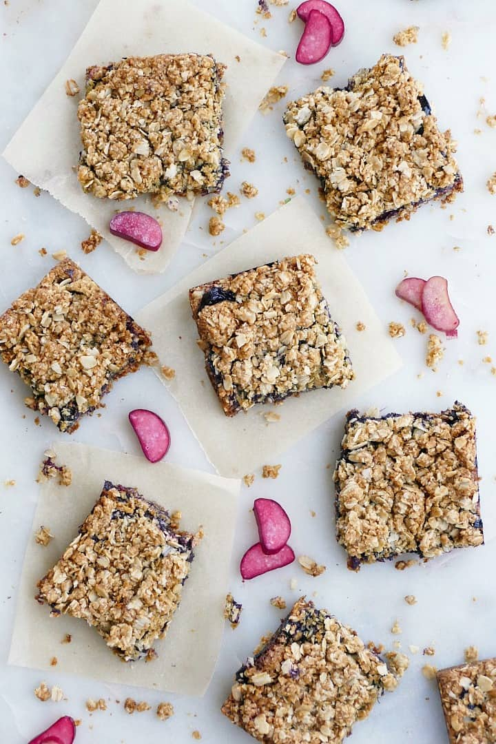 6 blueberry rhubarb bars on a white counter with oats and rhubarb slices