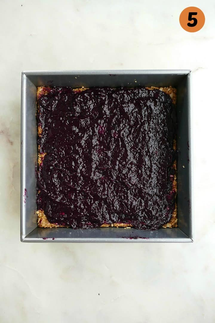 an oat base in a baking dish with a layer of blueberry rhubarb jam on top