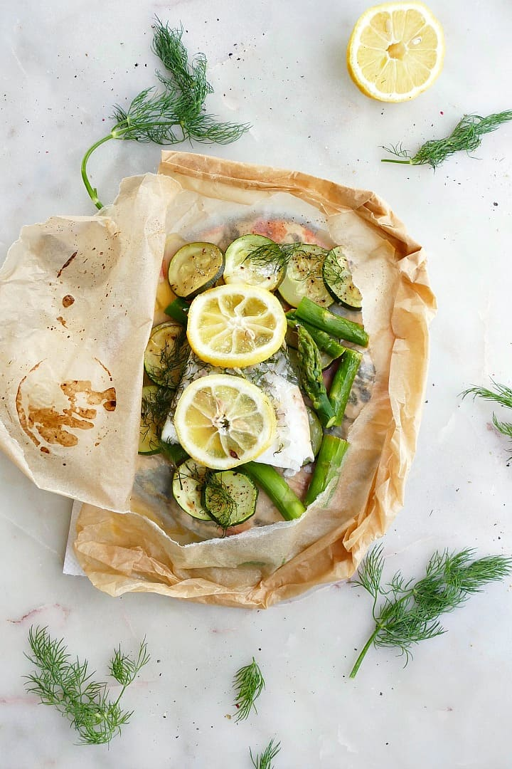 cod en papillote with lemon slices and green vegetables on a white counter