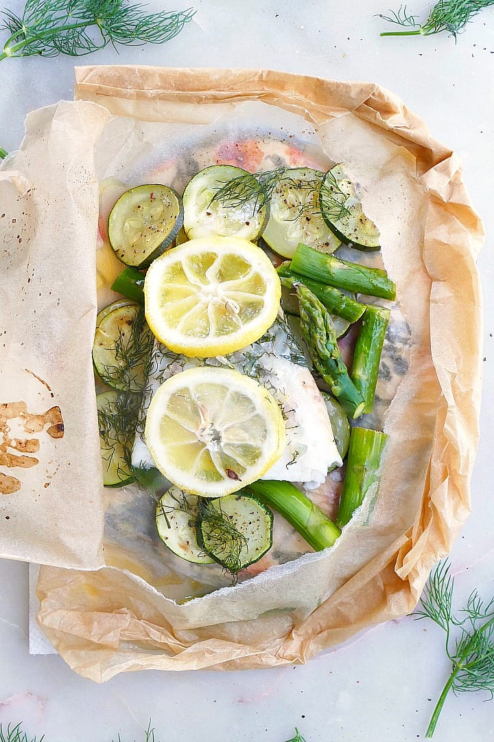 close up of cod en papillote with fresh lemon slices and dill in a parchment packet