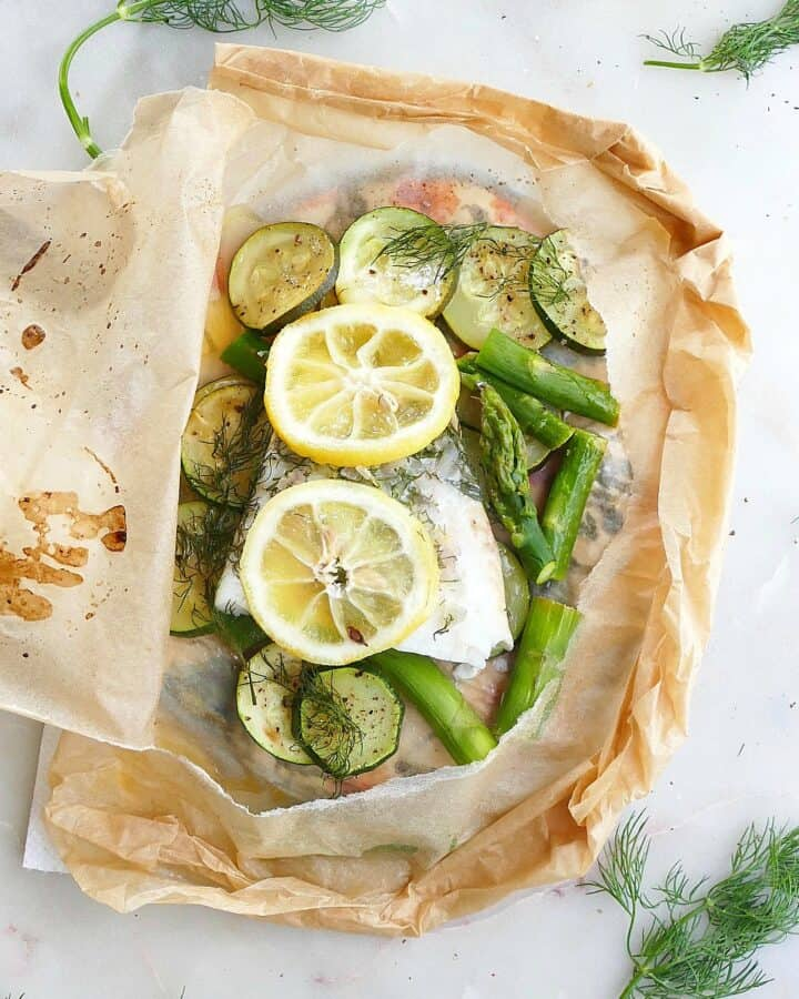 square image of cod en papillote with fresh lemon slices and dill