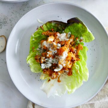 square image of buffalo cauliflower lettuce cups on a white plate