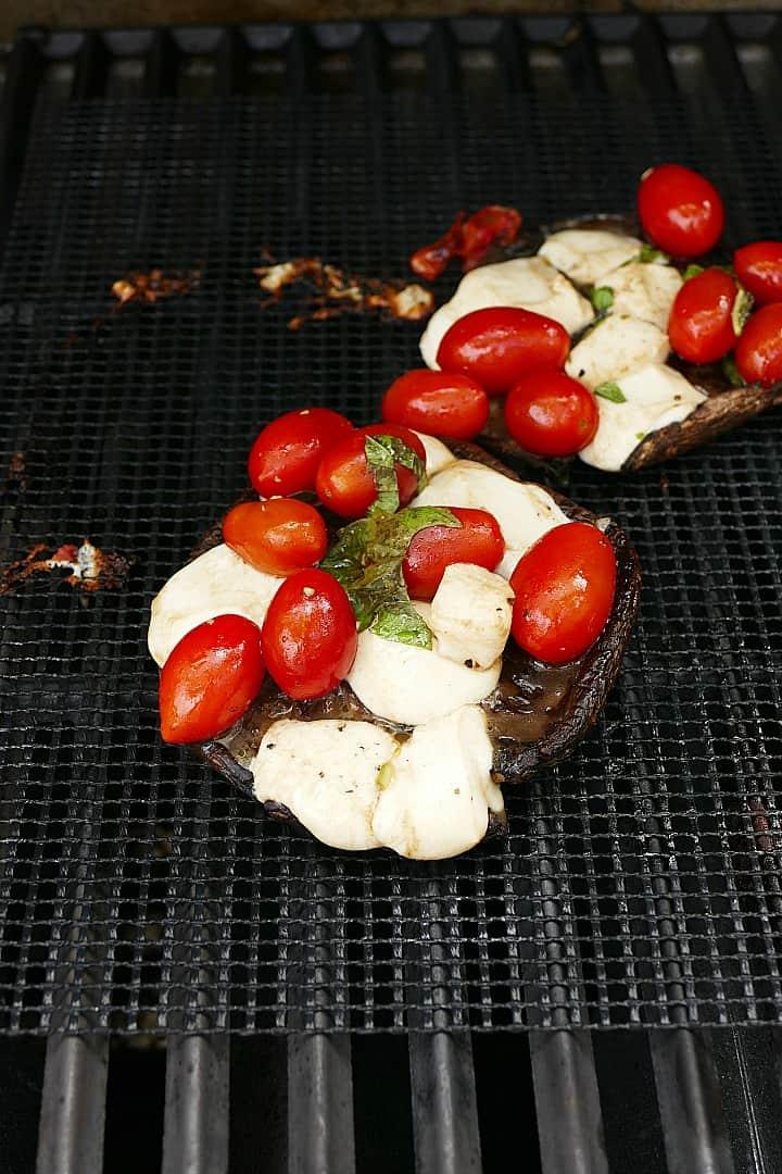 caprese stuffed portobello mushrooms on a mesh grill mat on a grill