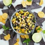 mango corn salsa in a gray bowl with blue and yellow chips surrounding it
