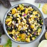 close-up of mango corn salsa in a gray bowl surrounded by chips and limes